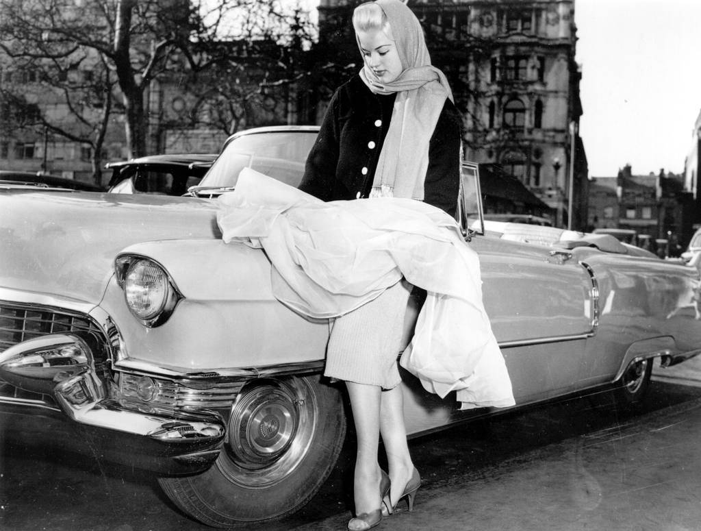 Diana Dors, with the Cadillac in which she arrived, at the Cannes Film Festival 1956 .jpg