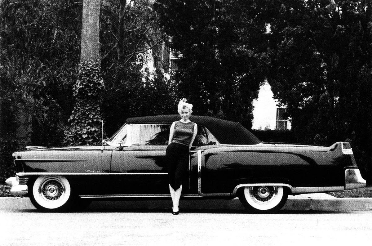 Marilyn Monroe poses in front of the black Cadillac that was gifted to her by 20th Century Fox.jpg