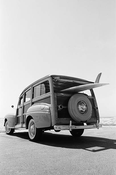 old-woodie-station-wagon-with-surfboard-picture-id182504870.jpg