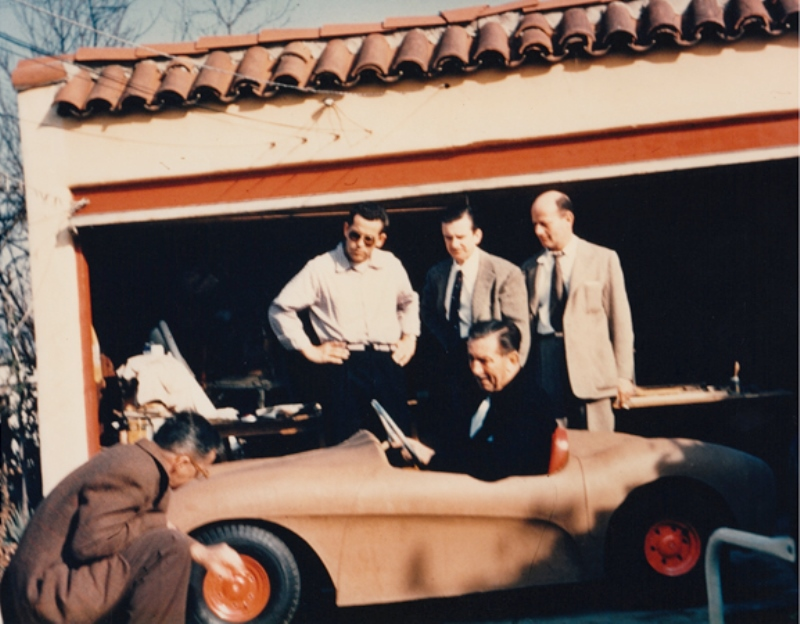 Walt Disney test driving Autopia prototype as Gurr looks on.jpg